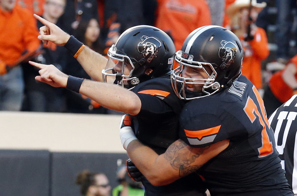 Photo - Oklahoma State's J.W. Walsh (4) and Michael Wilson (74) celebrate a Walsh touchdown in the third quarter during the college football game between the Oklahoma State Cowboys (OSU) and TCU Horned Frogs at Boone Pickens Stadium in Stillwater, Okla., Saturday, Nov. 7, 2015. Photo by Sarah Phipps, The Oklahoman