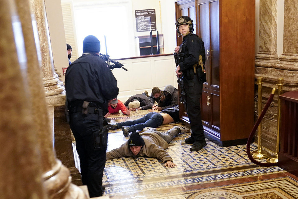 Photo - U.S. Capitol Police hold protesters at gun-point near the House Chamber inside the U.S. Capitol on Wednesday, Jan. 6, 2021, in Washington. (AP Photo/Andrew Harnik)