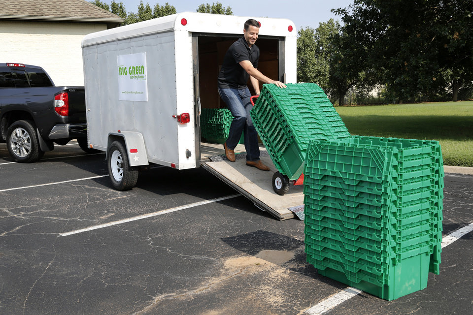 Photo -  Big Green Moving Boxes co-owner Steven Embree unloads moving boxes from a trailer Tuesday.