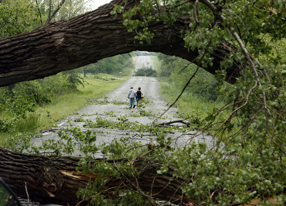 Photo - A couple walk down a residential road between downed trees aftera tornado struck near 156th street and Franklin Road on Sunday, May 19, 2013  in Norman, Okla. Photo by Steve Sisney, The Oklahoman