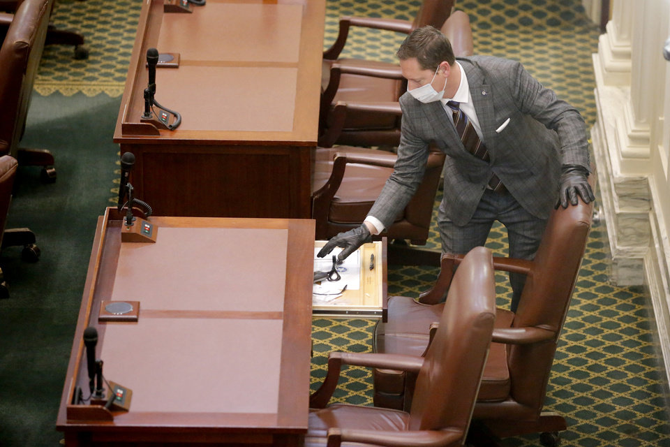 Photo - Rep. Brian Hill looks inside his desk before a special session of the House of Representatives at the state Capitol in Oklahoma City, Monday, April 6, 2020. A skeleton crew of lawmakers was allowed in the House chamber as others watched from their offices during a special session of the House of Representatives. [Bryan Terry/The Oklahoman]