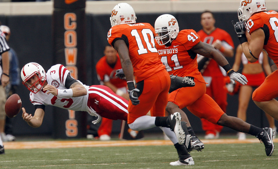 Photo - Nebraska's Taylor Martinez pitches the ball as he is pressured by OSU's Markelle Martin (10) and Orie Lemon (41) during the college football game between the Oklahoma State Cowboys (OSU) and the Nebraska Huskers (NU) at Boone Pickens Stadium in Stillwater, Okla., Saturday, Oct. 23, 2010. Photo by Sarah Phipps, The Oklahoman