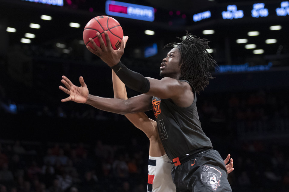 Photo - Oklahoma State guard Isaac Likekele (13) goes to the basket during the first half of an NCAA college semi final basketball game against the Syracuse in the NIT Season Tip-Off tournament, Wednesday, Nov. 27, 2019, in New York. (AP Photo/Mary Altaffer)