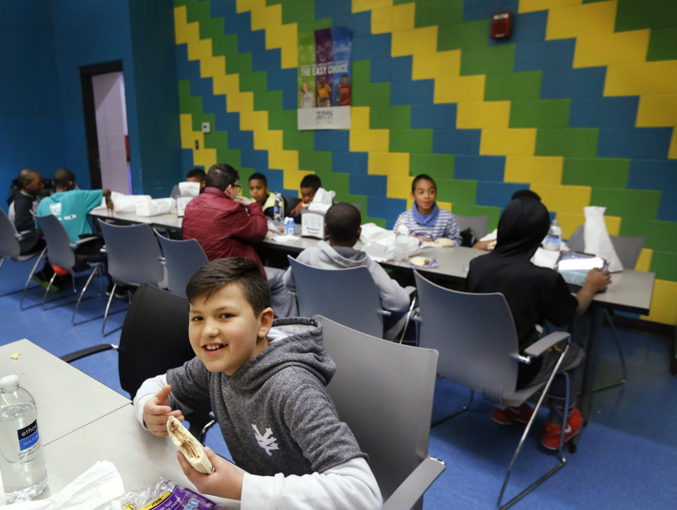 Photo - Students eat food from sack lunches given to them at a food truck provided by Oklahoma City Public Schools Nutrition Services on Monday, April 2, 2018. As a result of the teacher walkout, children who spent their day at the Boys and Girls Club of Oklahoma County  received free lunches from the school district. Photo by Jim Beckel, The Oklahoman