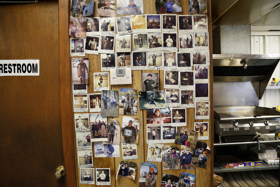 Photo -  Photos of anglers with their prize catches cover a wall between the restroom and the grill area inside Scotty's Blue River One Stop near Tishomingo. The store which sells burgers and bait is iconic among Blue River anglers. [PHOTO BY JIM BECKEL, THE OKLAHOMAN]