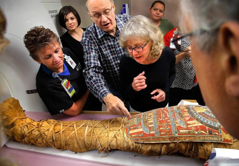 Photo - Omar Zuhdi, center, explains the meaning of the various hieroglyphics covering the torso of this Egyptian mummy known as Tutu Aug, 20, 2015. Listening to Zuhdi are CT technician Kelly Coffelt, far left, Leah Davison, background, and Megan Clement, right. Curators from the Mabee-Gerrer Museum of Art crated their two mummies and delivered them in 2015 to SSM Health St. Anthony Shawnee Hospital, where technicians performed CT scans on both corpses. CT, or CAT scans, are special X-ray tests that produce cross-sectional images of the body using X-rays and a computer. [Jim Beckel/The Oklahoman Archives]