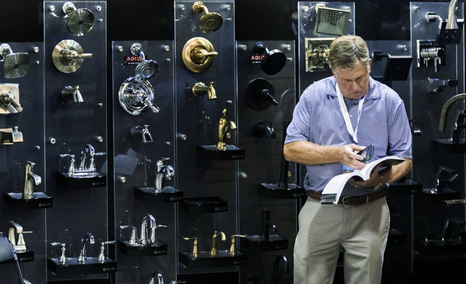 Photo -  Ted Schaefer of Delta Faucet Co. works the display booth during the Oklahoma Building Summit at Cox Convention Center on Wednesday. [PHOTO BY CHRIS LANDSBERGER, THE OKLAHOMAN]