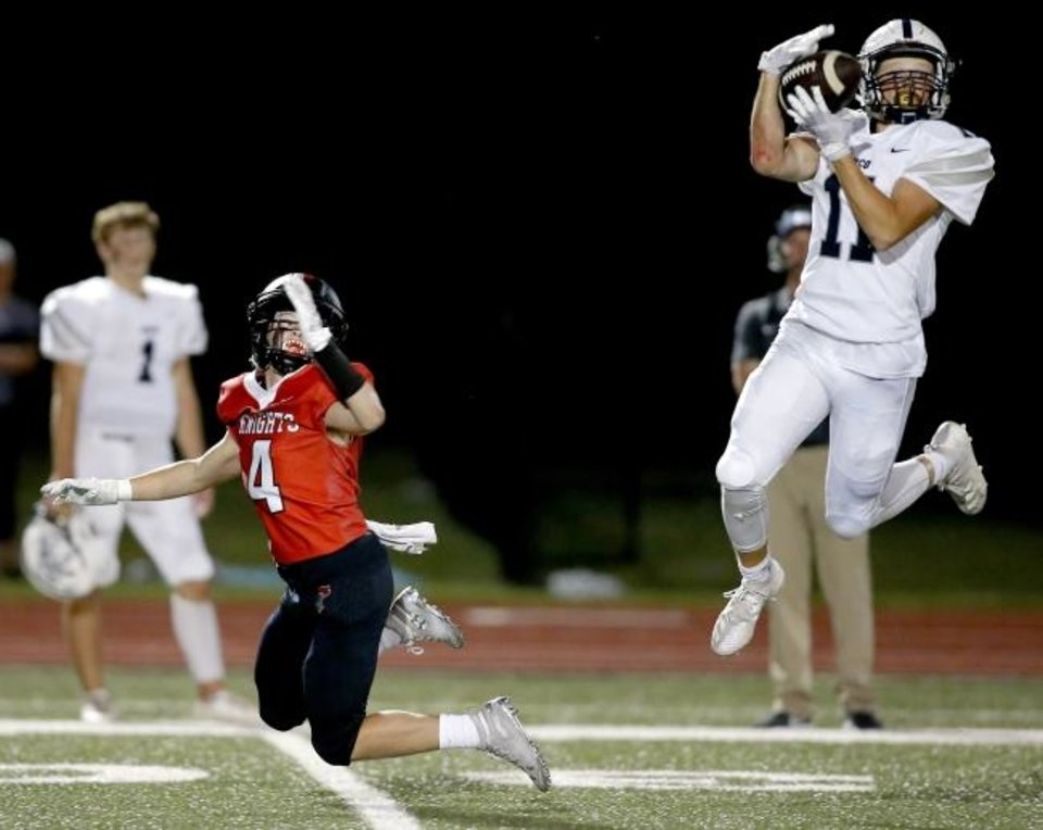 Photo -  Minco's Kenny Fouch intercepts a pass intended for Crossing Christian's Logan McGowan in the Bulldogs' 14-6 win Friday. [Bryan Terry/The Oklahoman]