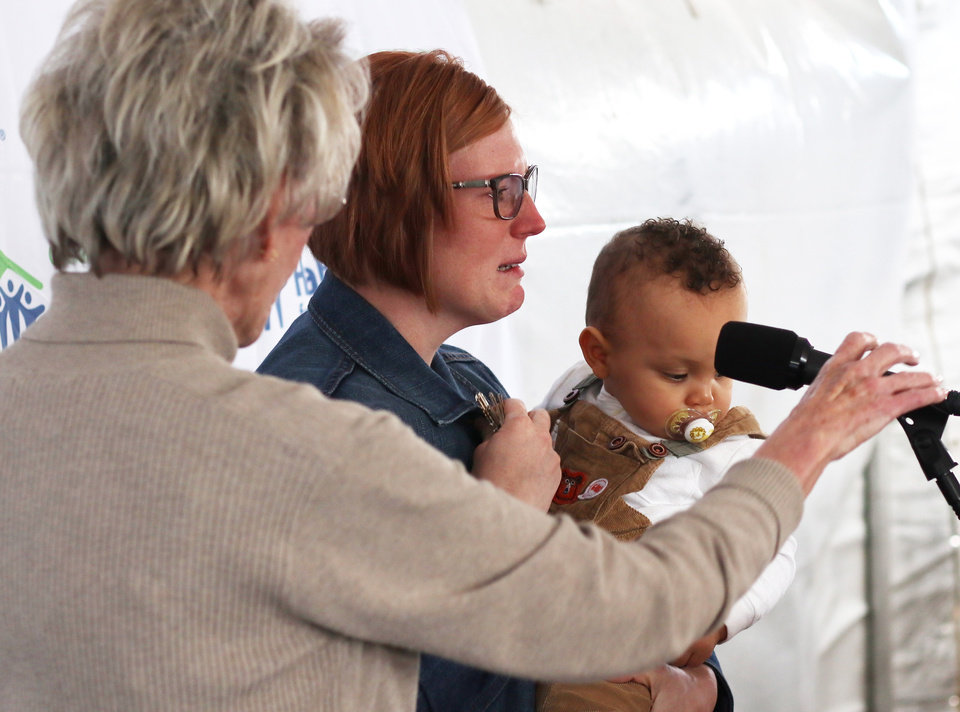 Photo - Ann Felton Gilliland adjust the mic for Brittani Githiri while she fights back tears after accepting the keys to the house. She is holding her one year old son, Piaget. Habitat for Humanity's 1,000 home, Monday, March 9, 2020.  [Photo by Doug Hoke/The Oklahoman]