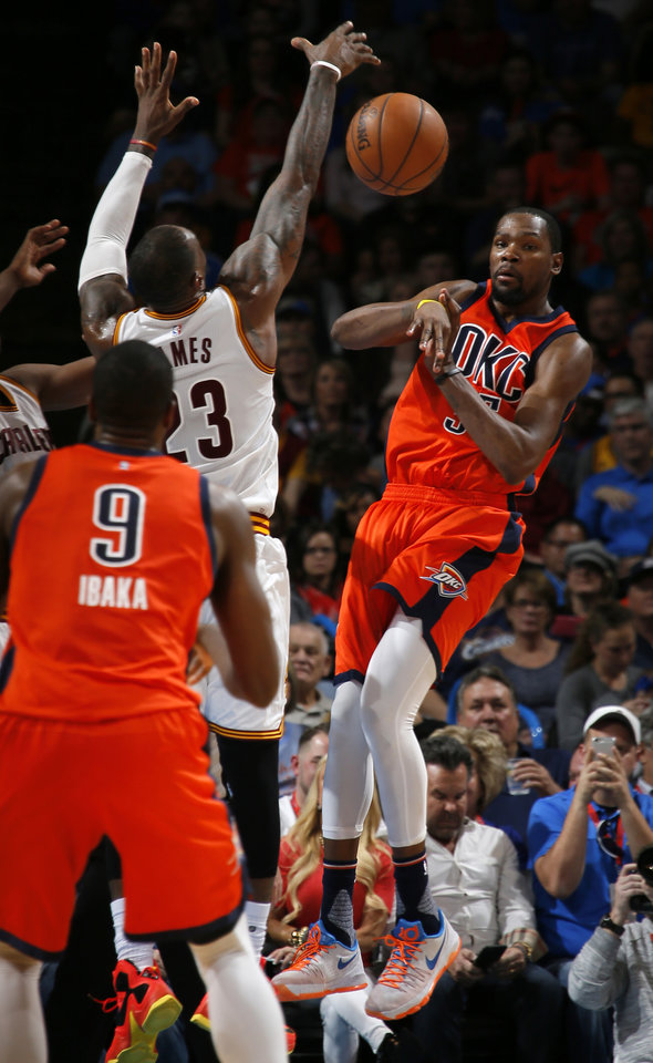 Photo - Oklahoma City's Kevin Durant (35) passes the ball over Cleveland's LeBron James (23) during an NBA basketball game between the Oklahoma City Thunder and the Cleveland Cavaliers at Chesapeake Energy Arena in Oklahoma City, Sunday, Feb. 21, 2016. Oklahoma City lost 115-92.  Photo by Bryan Terry, The Oklahoman