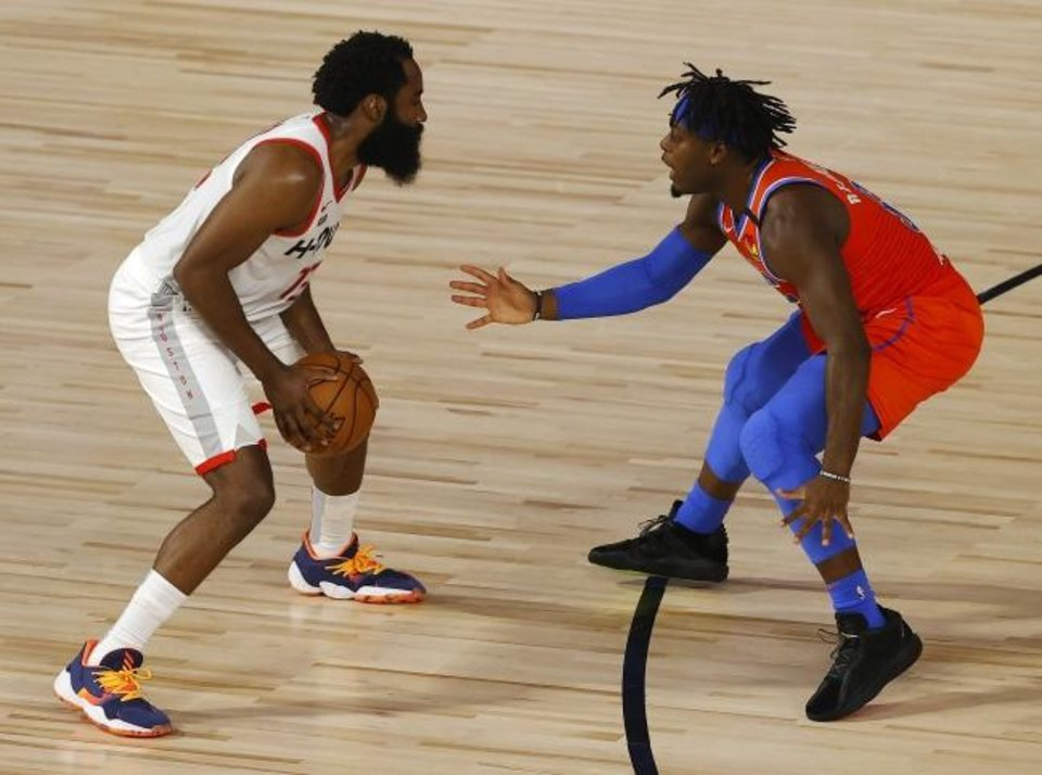 Photo -  Thunder guard Luguentz Dort, right, defense Rockets guard James Harden during Game 3 of their first-round playoff series on Aug. 22 in the NBA's Orlando bubble. [Mike Ehrmann/USA TODAY Sports]
