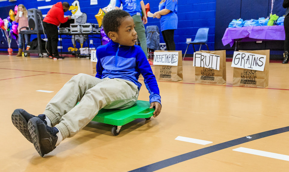 Photo - Edward Elementary second grader Alijah Pikes races backwards on a scooter for a food group challenge during the celebration of the classes achievements for the Wiggle Out Loud activity challenge at Edward Elementary School in Oklahoma City, Okla. on Friday, March 1, 2019. Photo by Chris Landsberger, The Oklahoman