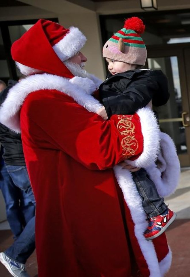 Photo -  Santa Claus holds Zack Huffer, 2, of Mustang, before delivering enrichment gifts to animals at The Oklahoma City Zoo and Botanical Garden.  [Sarah Phipps/The Oklahoman]