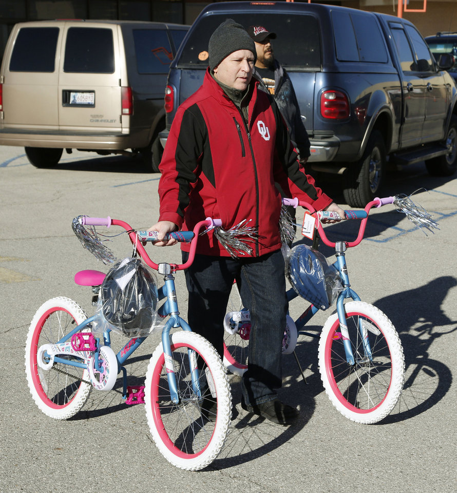 Photo -  Volunteer Kris Wallace walks a pair of bicycles to a recipient's car. [Photo by Paul Hellstern, The Oklahoman]