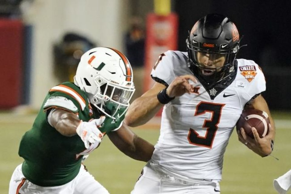 Photo -  Oklahoma State quarterback Spencer Sanders (3) tries to get past Miami linebacker Keontra Smith, left, during the Cowboys' 37-34 win in the Cheez-It Bowl on Dec. 29 in Orlando, Fla. [AP Photo/John Raoux]
