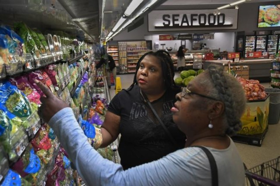 Photo -  Adrienne Dove, left, and her mother, Joanne Dove, shop for produce in May at a Giant store in Washington. Dove received a $20 produce coupon from her health-care clinic, where she goes to get treatment for hypertension. The produce [Michael S. Williamson/The Washington Post]
