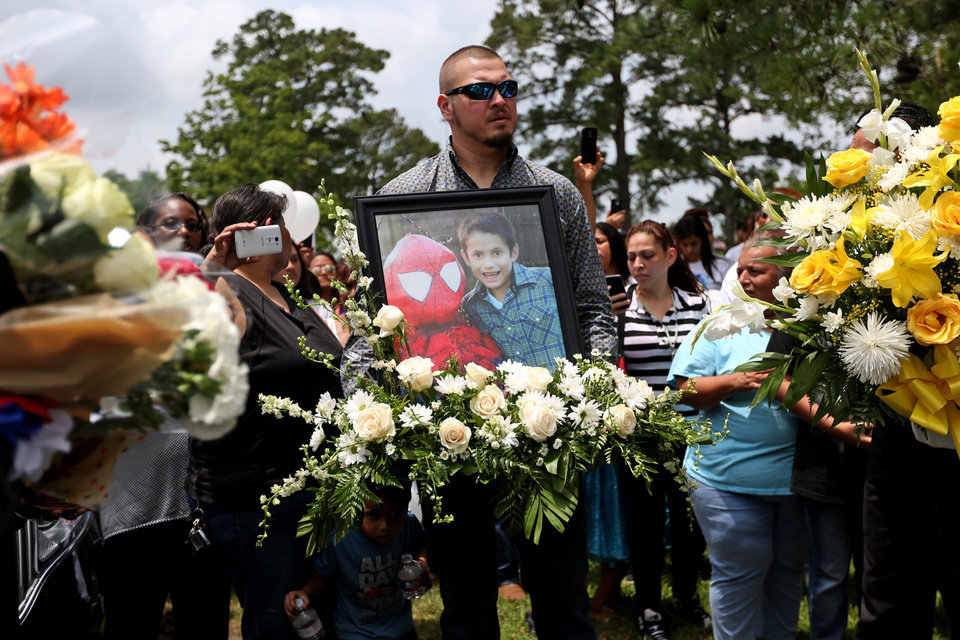 ... Photo - Flowers and a photo of Josue Flores to be placed at his grave site