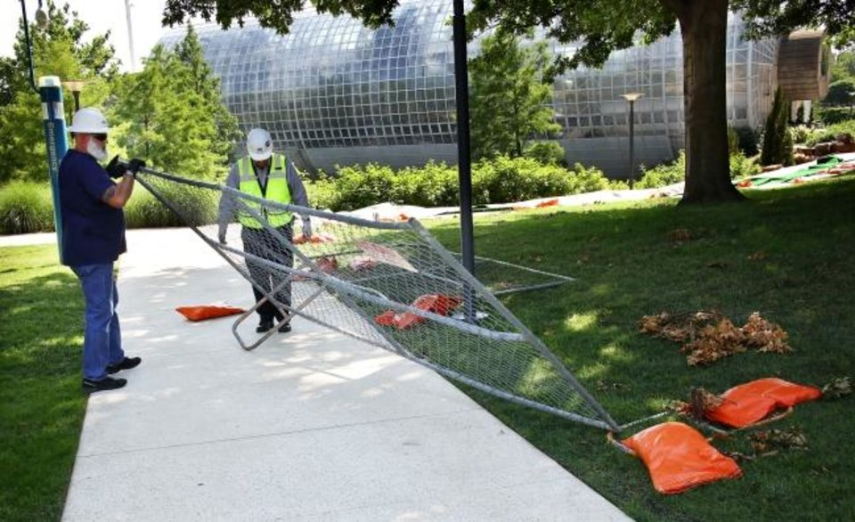 Photo -  Workers on Thursday remove the temporary fencing from the north side of the Myriad Botanical Gardens that had been in place since the Devon Energy Tower window washer incident. [Doug Hoke/The Oklahoman]