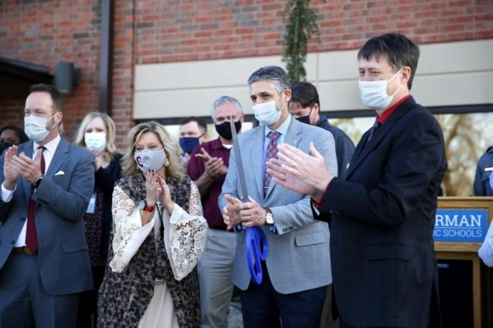 Photo -  Dr. Nick Migliorino, superintendent, center, claps after a ribbon cutting for Norman Public Schools' Dimensions Academy building that houses the district's alternative education program in Norman, Okla., Tuesday, Jan. 5, 2021. [Sarah Phipps/The Oklahoman]