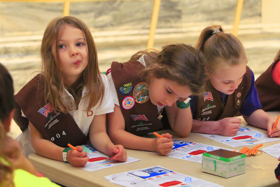 Photo -  Hailey Buckwalter, left, Avery Terrill and Aliyah Jones from Edmond Brownie Troop 904 work on a project as Girl Scouts spend a morning at the state Capitol.  [Photo by Paul Hellstern, The Oklahoman]
