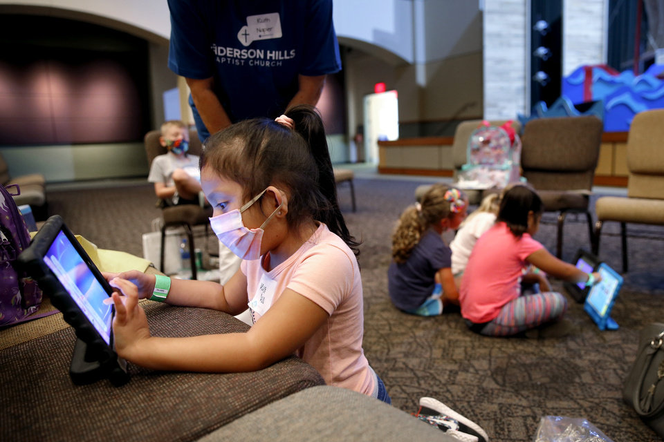 Photo - Keyla Rojo, 5, uses a tablet inside Henderson Hills Baptist Church in Edmond, Okla., Wednesday, Aug. 26, 2020. The church has begun offering Edmond school students a place to go on Wednesdays to get homework help, use the free wi-fi for virtual learning, free lunch and other activities. [Bryan Terry/The Oklahoman]