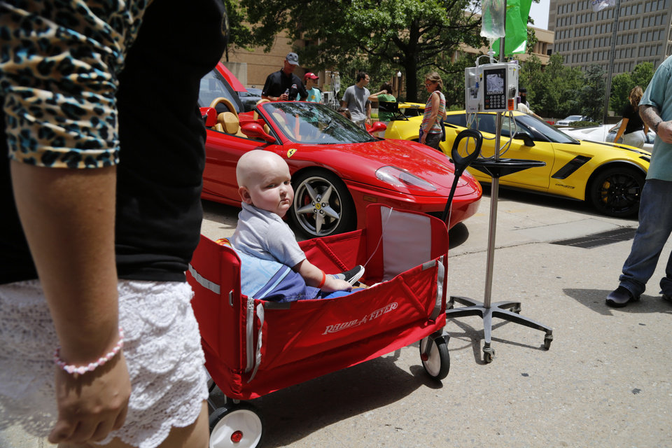 Photo - Denton Padgett, 4, came out to see the cars in his wagon, pulled by his mom and dad, Ashley and Dustin Padgett, of Chickasha. Redline4Kids is a new nonprofit that helps connect kids in the hospital with a chance to see cool cars. Photo by Jim Beckel, The Oklahoman