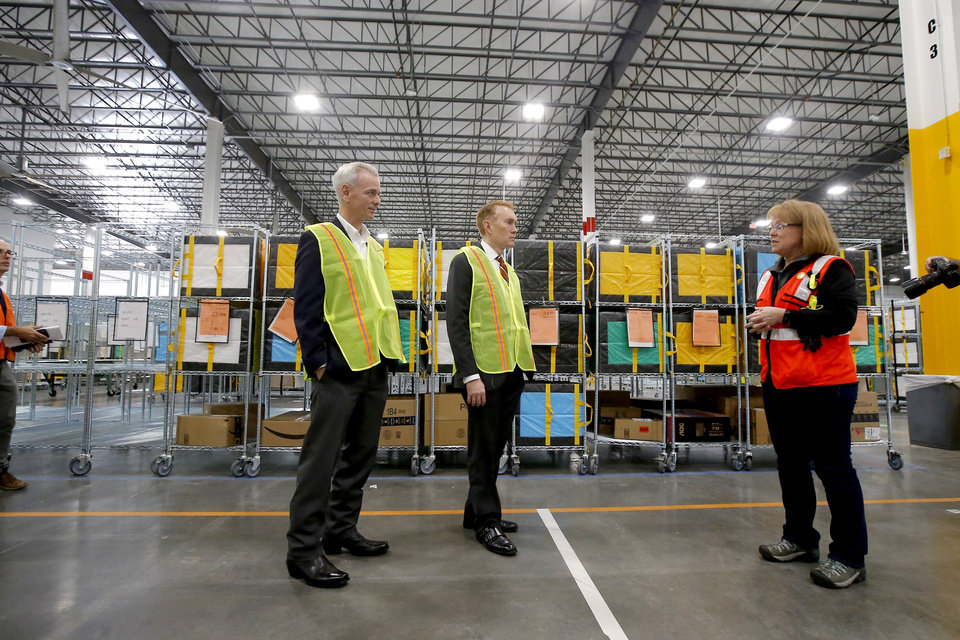 Photo - U.S. Rep. Steve Russell, left, and U.S. Sen. James Lankford talk with Paula Munter of Amazon during a tour of the new Amazon Delivery Center in Oklahoma City, Tuesday, Oct. 23, 2018. Photo by Bryan Terry, The Oklahoman