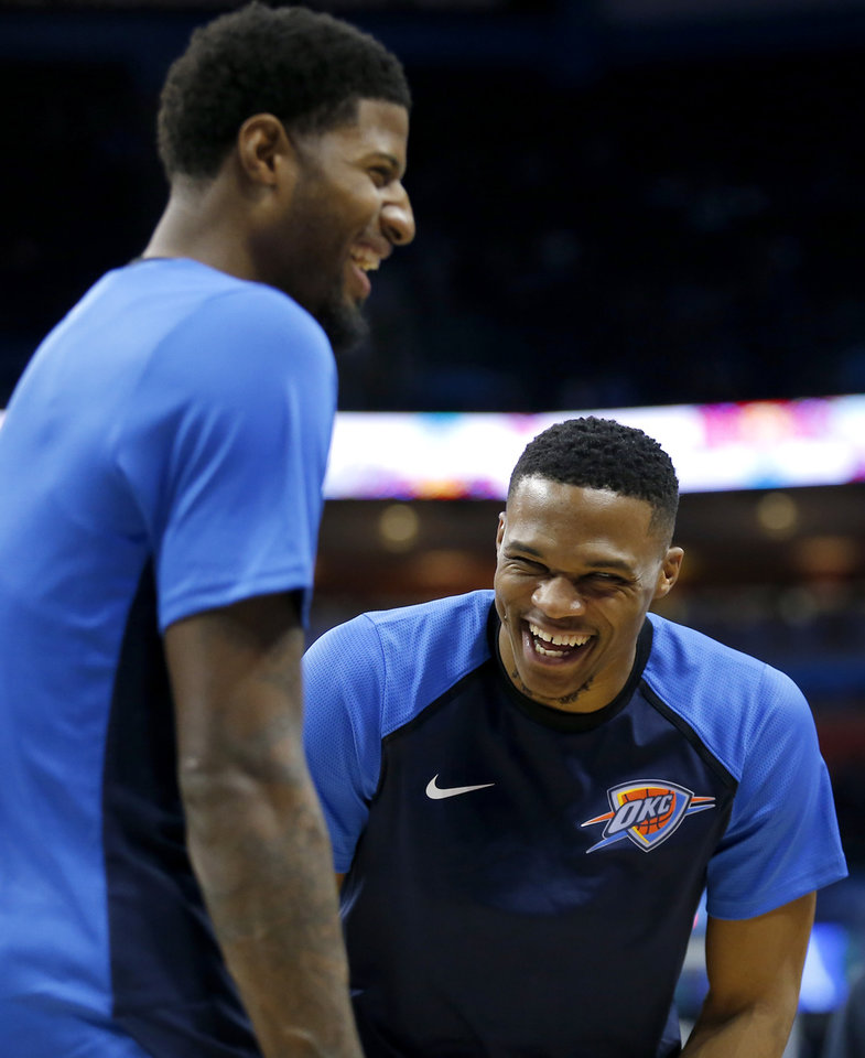Photo - Oklahoma City's Russell Westbrook (0) and Oklahoma City's Paul George (13) laugh during a time out during a  NBA preseason game between the Oklahoma City Thunder and Milwaukee Bucks at Chesapeake Energy Arena in Oklahoma City,  Tuesday, Oct. 9, 2018. Iowa State won 48-42. Photo by Sarah Phipps, The Oklahoman