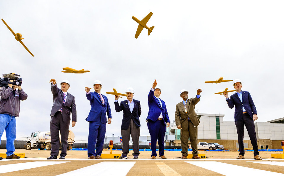 Photo -  Officials stand on the groundbreaking runway Friday to launch a ceremonial plane during a ceremony for the official launch of the Will Rogers World Airport Terminal Expansion Project at the airport in Oklahoma City. [Chris Landsberger/The Oklahoman]