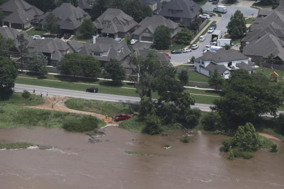 Photo -  Flood water encroach homes near 118th and Delaware on the Arkansas river on Wednesday, May 22, 2019. Authorities on Wednesday encouraged people living along the Arkansas River in the Tulsa suburb of Bixby and low-lying areas near creeks both north and south of Okmulgee, about 35 miles (56 kilometers) south of Tulsa. to leave their homes. (Tom Gilbert/Tulsa World via AP)