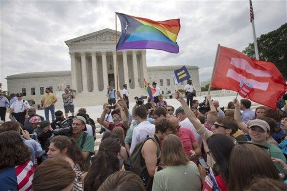 Photo - The crowd reacts as the ruling on same-sex marriage was announced outside of the Supreme Court in Washington, Friday June 26, 2015. The Supreme Court declared Friday that same-sex couples have a right to marry anywhere in the US. (AP Photo/Jacquelyn Martin)