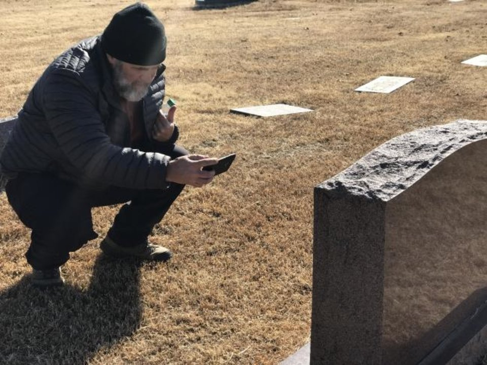 Photo -  Marde Burke takes a picture of a headstone at Trice Hill during the Save A Cemetery project at Trice Hill Cemetery, 5101 N Coltrane. [Carla Hinton/The Oklahoman]
