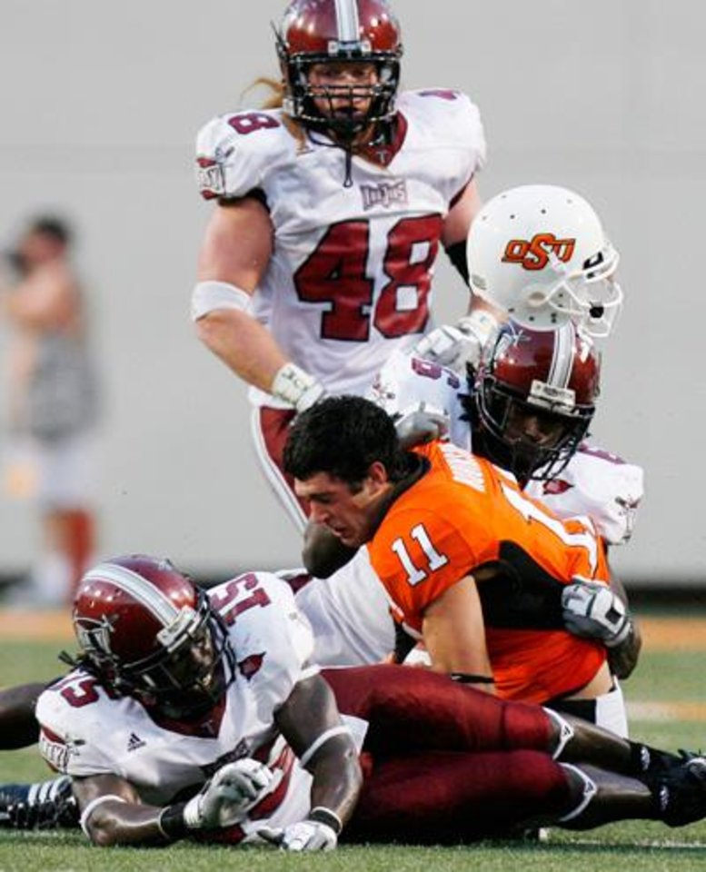 Photo -  Zac Robinson's helmet flies off at the end of a run as he is sandwiched by defenders at the Oklahoma State University (OSU) college football game against Troy University (TU) Saturday, Sept 27, 2008 at Boone Pickens Stadium in Stillwater, Oklahoma. BY SARAH PHIPPS, THE OKLAHOMAN.