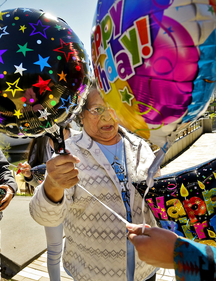 Photo - Geneva Foote picks out a balloon as she prepares to release the balloon in honor of her grandson Bradley Wahnee, who was killed in 2009 during a drive by shooting, to mark his birthday at the Myriad Botanical Gardens in Oklahoma City, Okla. on Monday, March 21, 2016. The family releases balloons every year on Bradley's birthday and the date he was killed.  Photo by Chris Landsberger, The Oklahoman