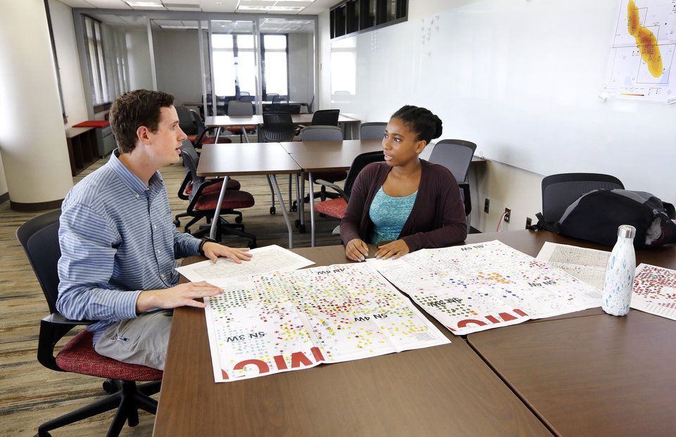 Photo -  OU students Andrew Oakes and Zaharaou Sylla, both seniors majoring in petroleum engineering, discuss data on geological maps they are consulting in the new Ronnie Irani Center for Energy Solutions on the 14th floor of Sarkey's Energy Center on the University of Oklahoma campus. [Photo by Jim Beckel, The Oklahoman]