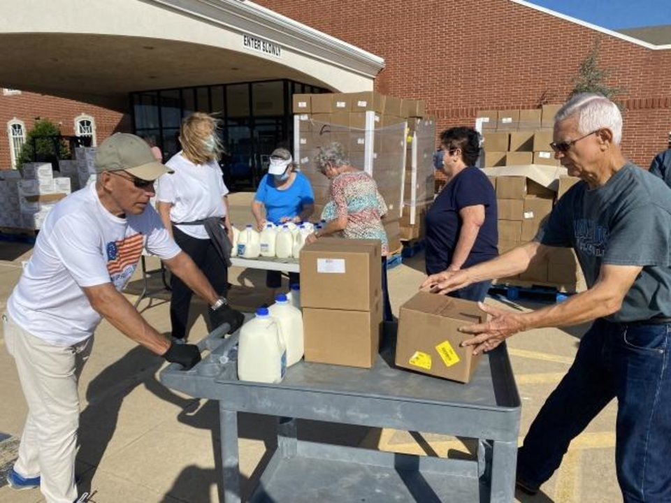 Photo -  Volunteers and staff at Southern Hills Baptist Church prepare to give away milk and other food items at a food distribution event at the church, 8601 S Pennsylvania. [Jeremy Johnson]