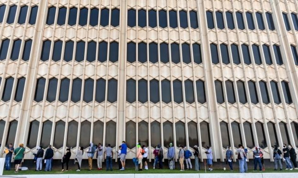 Photo -  A line of people stretches around sides of the headquarters building of the Oklahoma Employment Securities Commission on Friday as hundreds of people line up there each morning seeking to get help with their unemployment claim payments.   [Chris Landsberger/The Oklahoman]