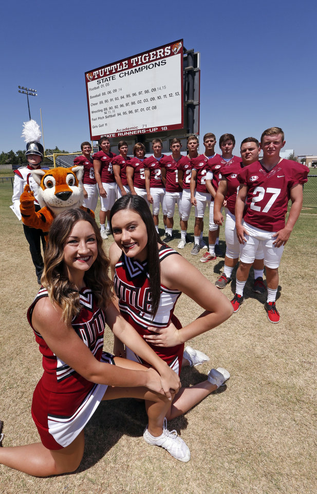 Photo - Tuttle fans show their school spirit near the high school football field on Tuesday, Aug. 16, 2016 in Tuttle, Okla.  Band member is Allyson Campbell.  Cheerleaders are Kylea Wilmot, left, and Lauren Robinson.  The mascot is Murphy Cornwell.  Photo by Steve Sisney, The Oklahoman