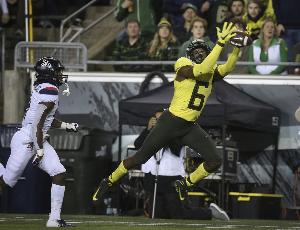 Photo - Oregon's Juwan Johnson, right, pulls down a Justin Herbert pass on his way to a touchdown ahead of Arizona's Christian Roland-Wallace, left, during the second quarter of an NCAA college football game Saturday, Nov. 16, 2019, in Eugene, Ore. (AP Photo/Chris Pietsch)