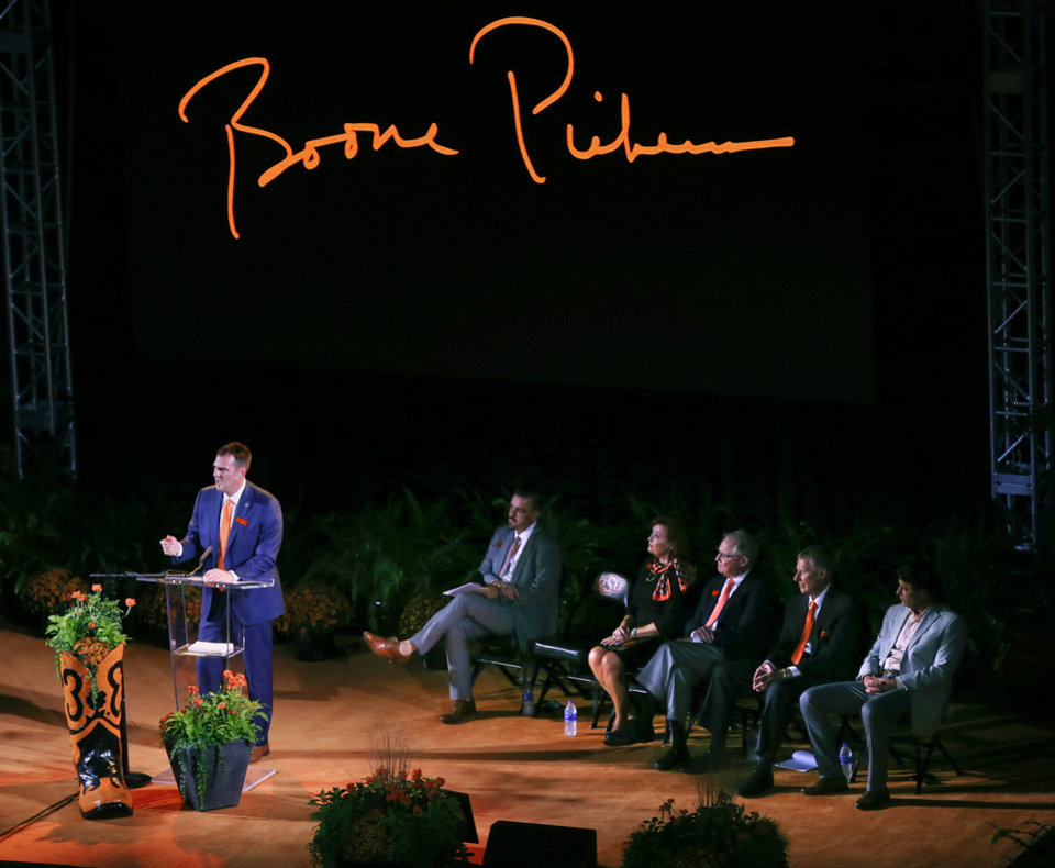 Photo - From left, Gov. Kevin Stitt speaks as OSU senior associate athletic director Larry Reece, OSU philanthropist Anne Greenwood, OSU president Burns Hargis, OSU athletic director Mike Holder and OSU football coach Mike Gundy sit on stage during the Celebration of Life for OSU alumnus and benefactor Boone Pickens at Gallagher-Iba Arena in Stillwater, Okla., Wednesday, Sept. 25, 2019. [Nate Billings/The Oklahoman]