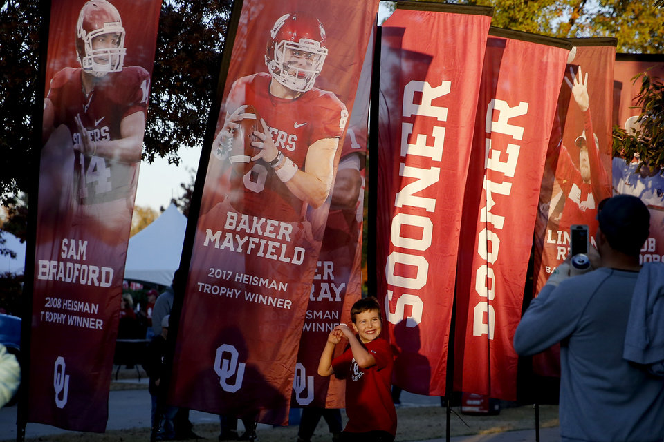 Photo - Miles Wasson, 11, poses in front of banners outside the stadium before an NCAA football game between the University of Oklahoma Sooners (OU) and the Iowa State University Cyclones at Gaylord Family-Oklahoma Memorial Stadium in Norman, Okla., Saturday, Nov. 9, 2019. [Bryan Terry/The Oklahoman]