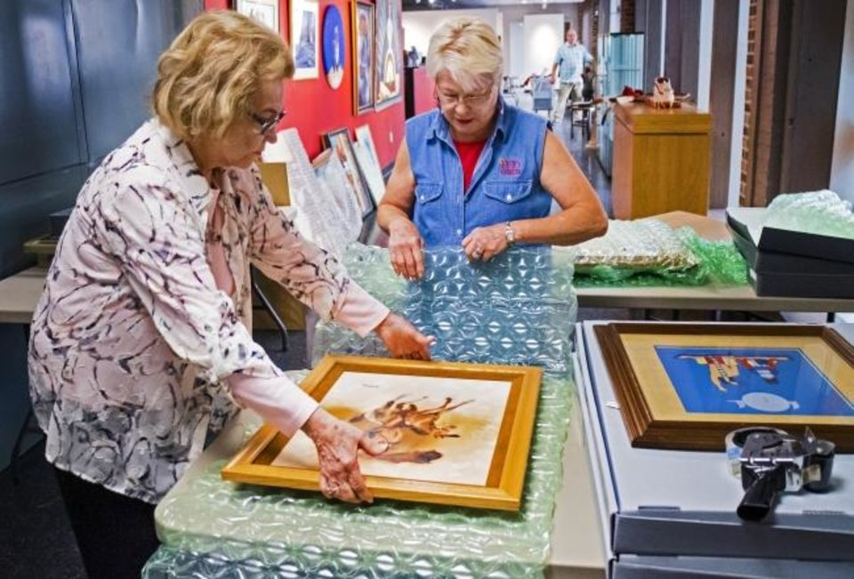 Photo -  Lou Kerr and Teri Stanek, from left, work to pack artwork at the Red Earth Art Center in Oklahoma City.  [Chris Landsberger/The Oklahoman]