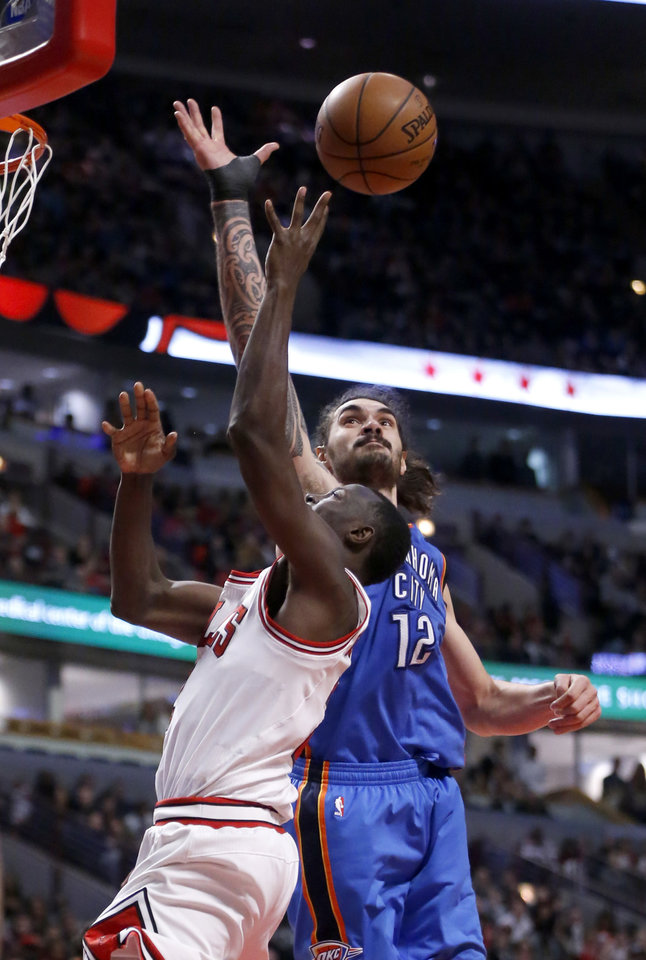 Photo - Oklahoma City Thunder's Steven Adams (12) blocks the shot of Chicago Bulls' Jerian Grant during the second half of an NBA basketball game Monday, Jan. 9, 2017, in Chicago. The Thunder won 109-94. (AP Photo/Charles Rex Arbogast)