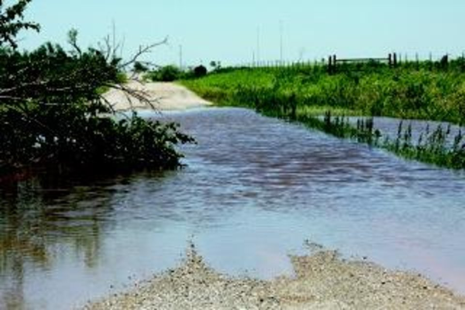 Photo - A portion of Radio Road south of Interstate 40 flooded Saturday after the May 31 tornado and storm went through El Reno. Travis Miller