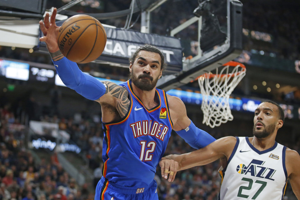 Photo - Oklahoma City Thunder center Steven Adams (12) reaches for the ball as Utah Jazz center Rudy Gobert (27) watches during the first half of an NBA basketball game Wednesday, Oct. 23, 2019, in Salt Lake City. [AP Photo/Rick Bowmer]