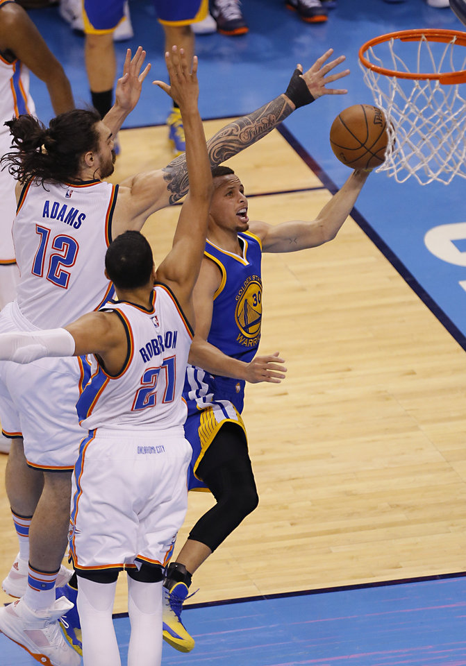 Photo - Oklahoma City's Steven Adams (12), Andre Roberson (21) defend as Golden State 's Stephen Curry (30) goes up for a basket during Game 3 of the Western Conference finals in the NBA playoffs between the Oklahoma City Thunder and the Golden State Warriors at Chesapeake Energy Arena in Oklahoma City, Sunday, May 22, 2016. Photo by Sarah Phipps, The Oklahoman