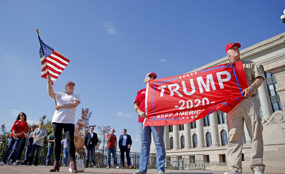 Photo - Gayla Whitten, right, Teresa Dickerson,  middle, and Rick Dickerson hold flags during a rally for President Trump at the Oklahoma state Capitol in Oklahoma City,  Saturday, Nov. 7, 2020. [Sarah Phipps/The Oklahoman]