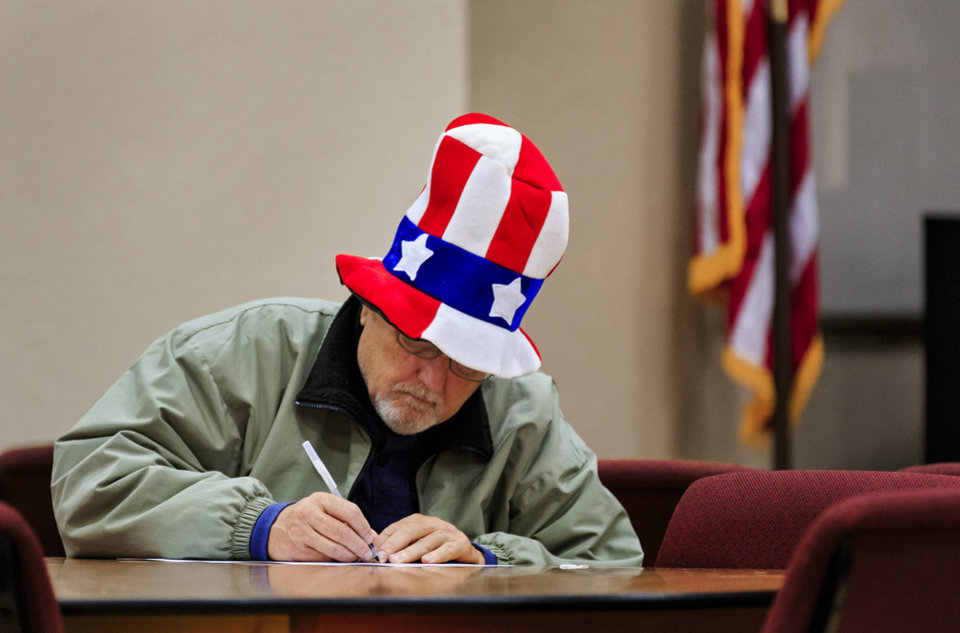 Photo - Mike Ryder wears his patriotic hat as he cast his vote on election day at the International Pentecostal Assembly in Yukon, Okla. on Tuesday, Nov. 6, 2018. Photo by Chris Landsberger, The Oklahoman