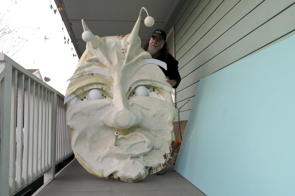 Photo -  Thom Karamus shows his paper mache head of the hookah-smoking caterpillar from