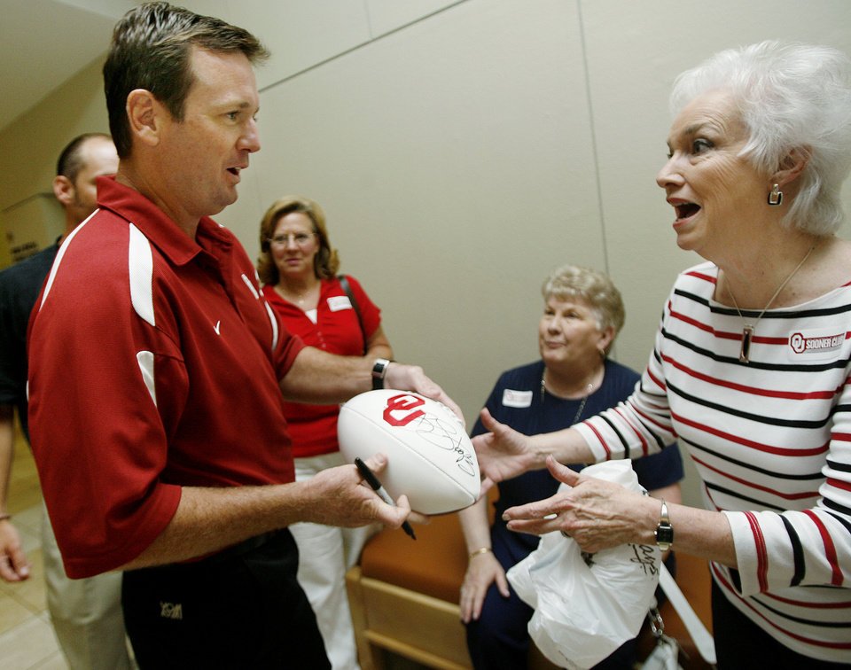 Photo - University of Oklahoma college football coach Bob Stoops signs a football for Rodena Cornell during the last stop of the OU Caravan at the National Cowboy & Western Heritage Museum on Thursday, August 2, 2007.  By Bryan Terry, The Oklahoman ORG XMIT: KOD